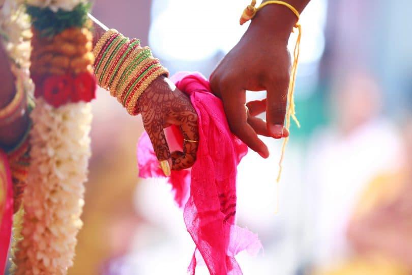 Mãos unidas por um pano rosa em um casamento hindu.