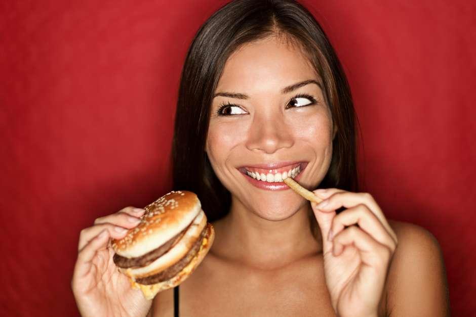 mulher comendo hamburguer e batata frita