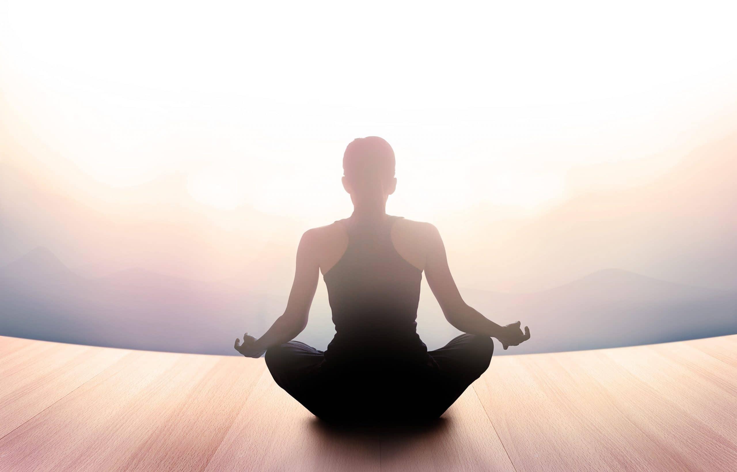 Mulher meditando de costas em uma sala vazia e bem iluminada.