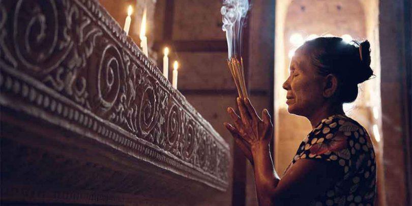 Mulher segurando incensos em sinal de oração dentro de um templo.