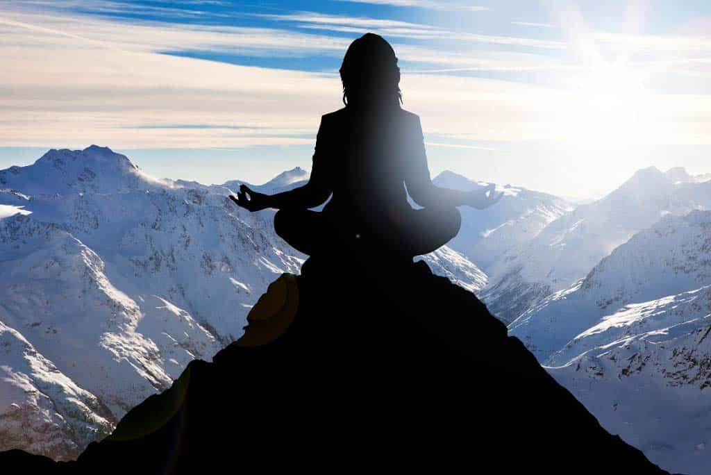 Mulher meditando no pico de uma montanha observando o horizonte cheio de outras montanhas nevadas com o sol ao fundo.