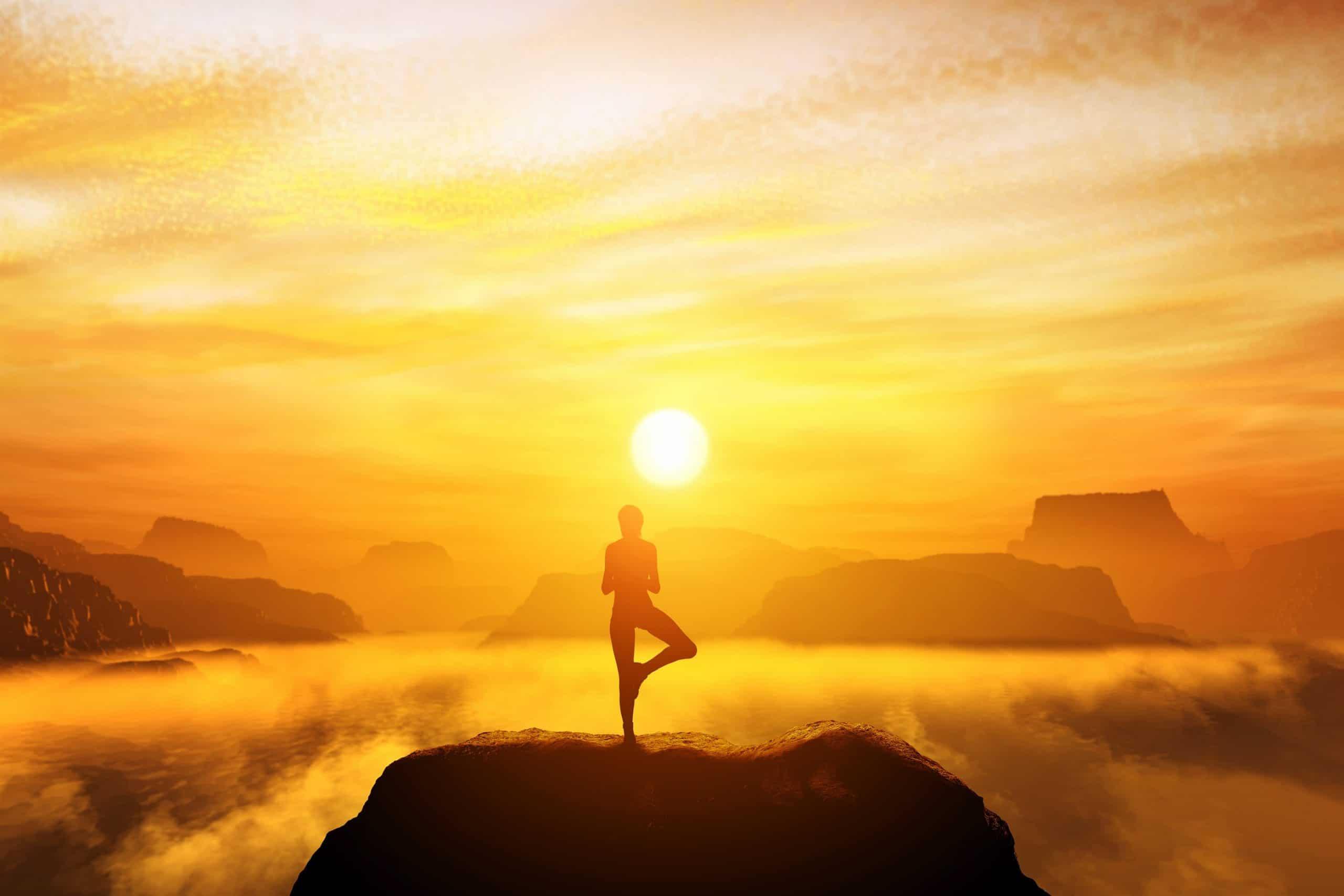 Pessoa praticando yoga no topo de uma montanha sob o pôr-do-sol.