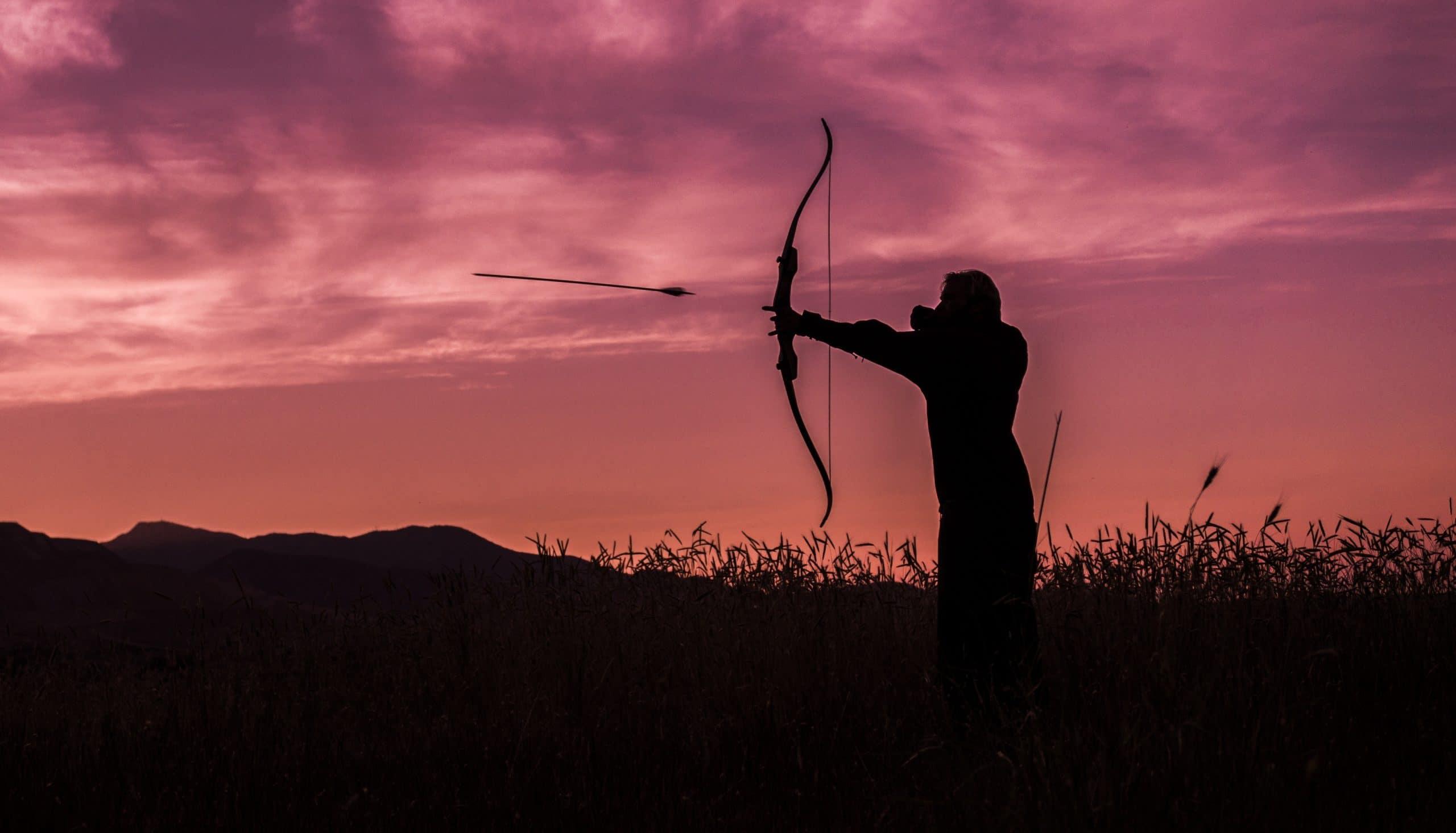 Silhueta de um arqueiro lançando sua flecha.