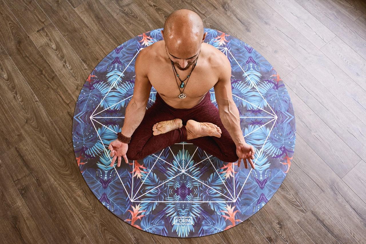 Homem sentado em tapete redondo em posição de meditação visto de cima