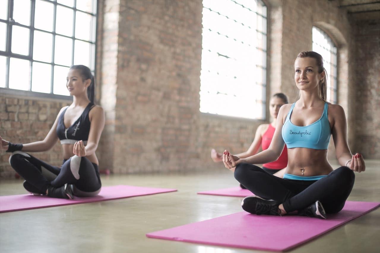 Mulheres sentadas em posição de meditação meditando juntas