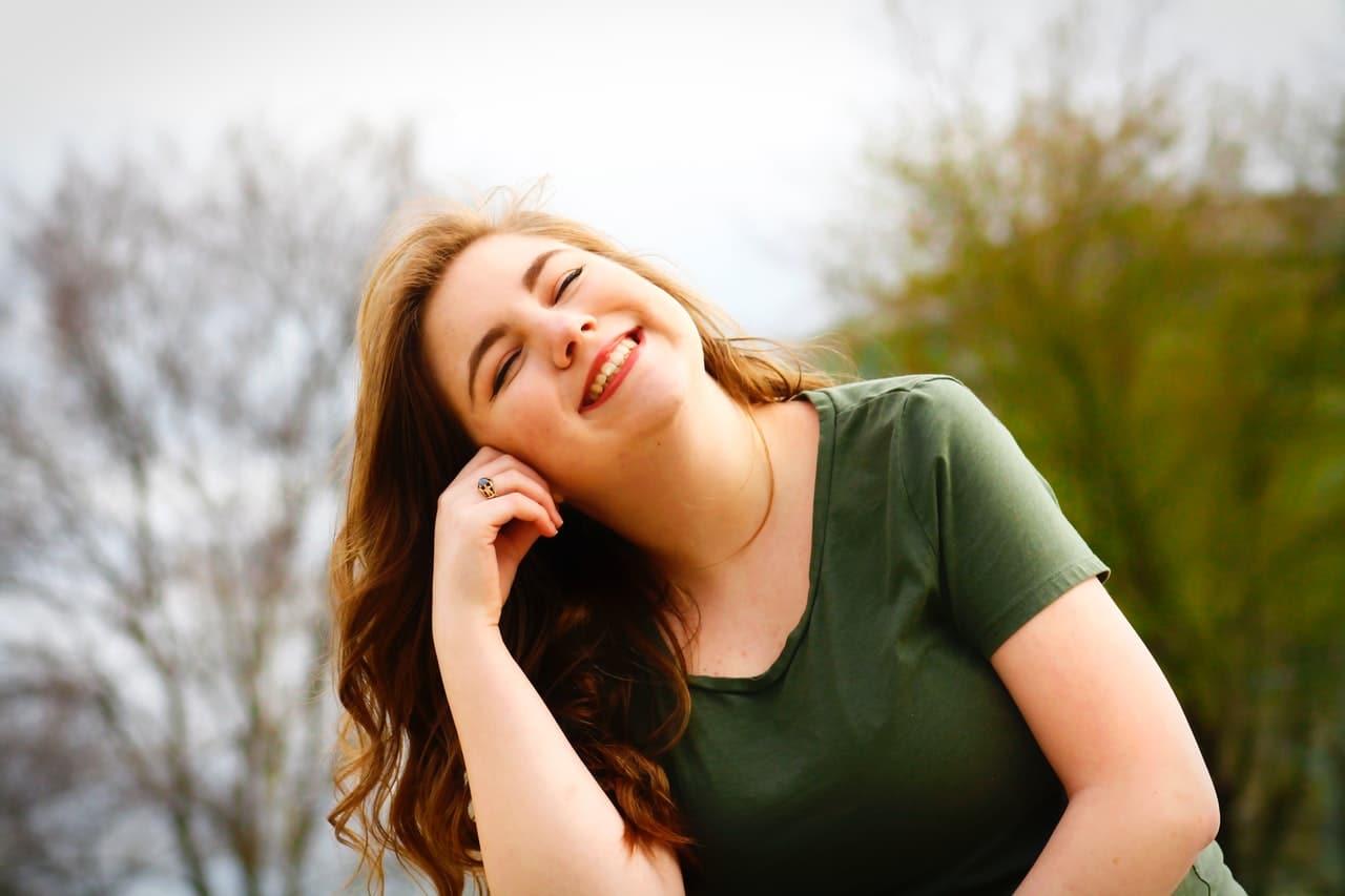 Mulher sorrindo com olhos fechados iluminada pelo sol