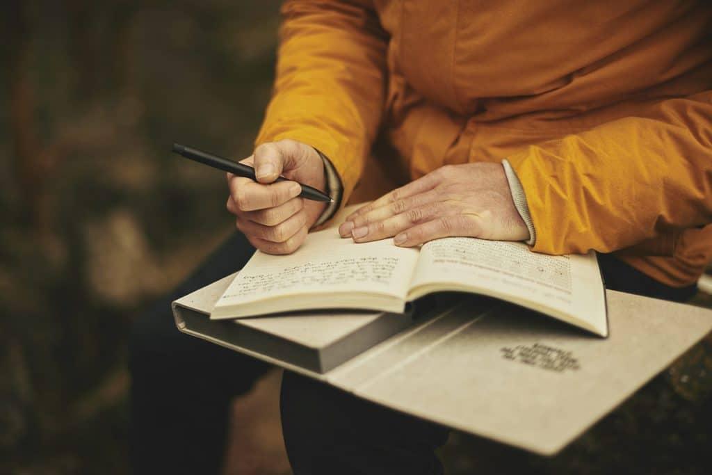 Homem vestindo uma blusa amarela. Ele está sentado em um local aberto. O foco da imagem é um caderno que está apoiado em seu colo e ele está escrevendo algo.