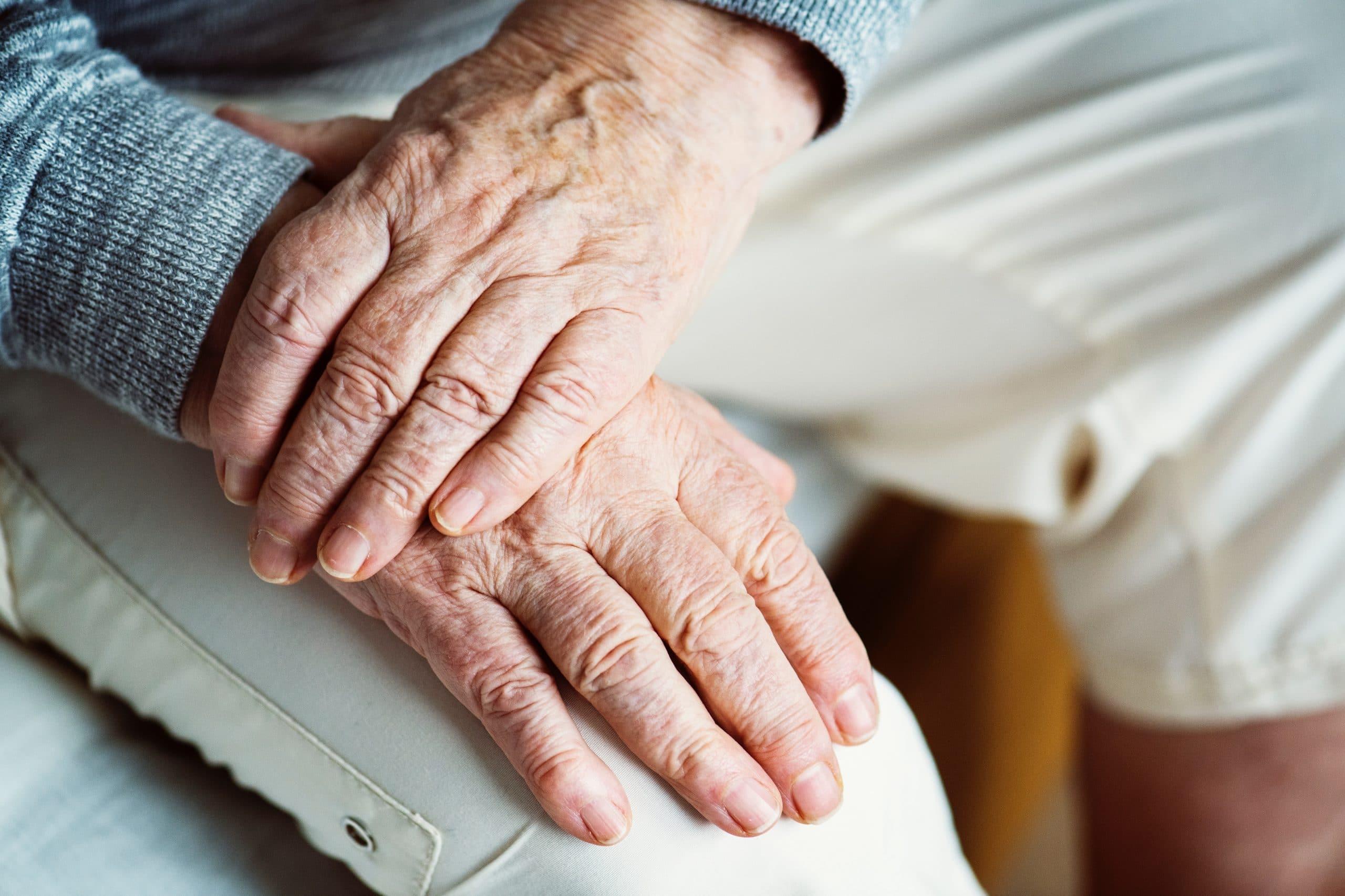 Mãos de idoso juntas.