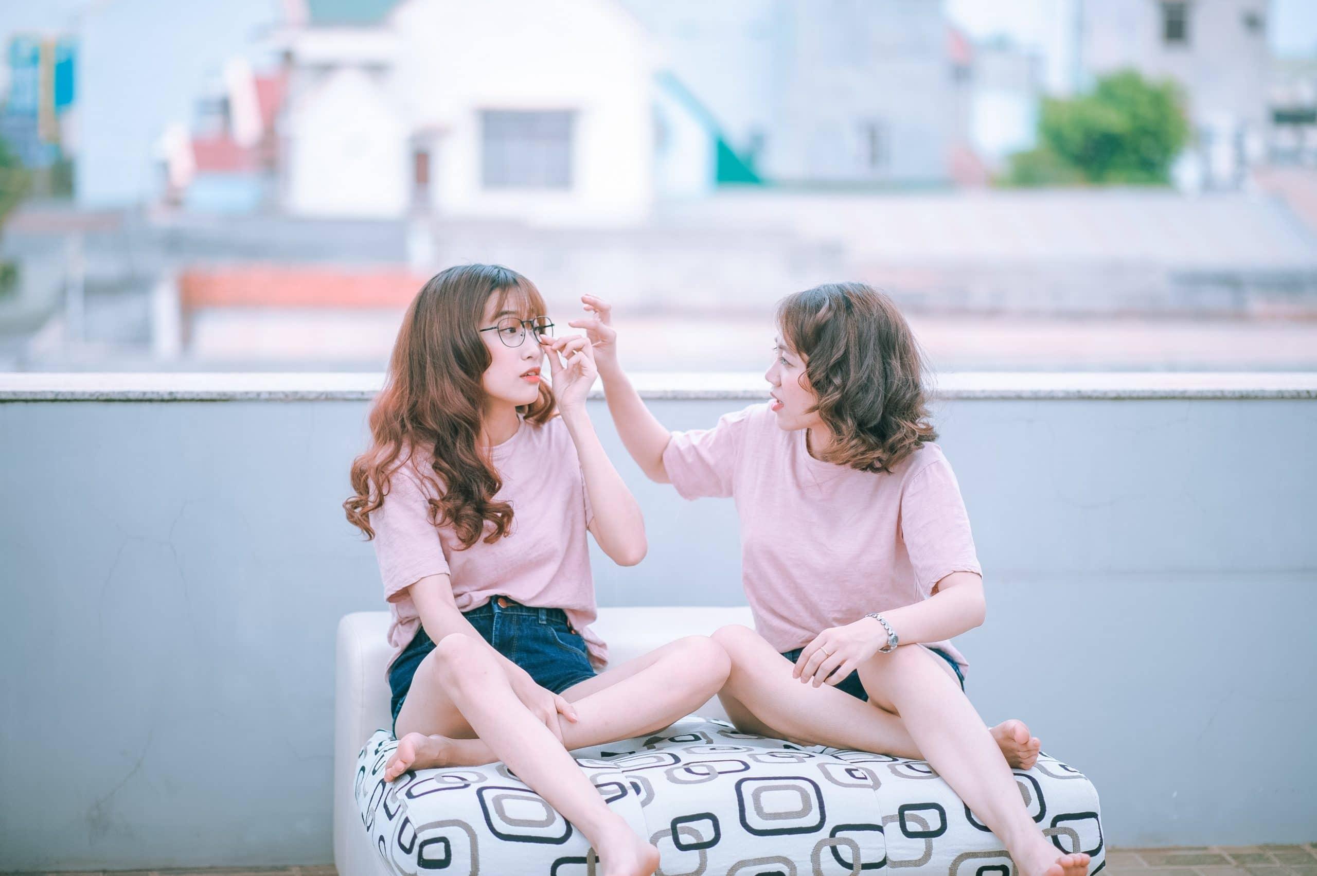 Duas mulheres conversando sentadas em um banco. Uma delas está arrumando o óculos da outra.