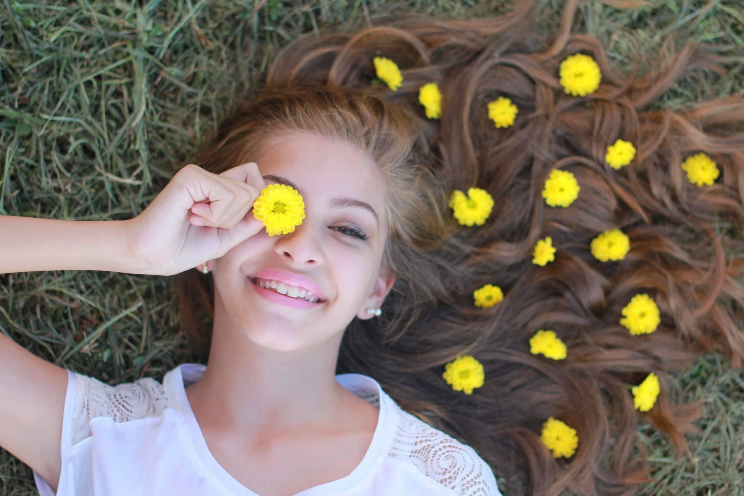 Menina deitada com cabelo pela grama e flores amarelinhas espalhadas pelo cabelo
