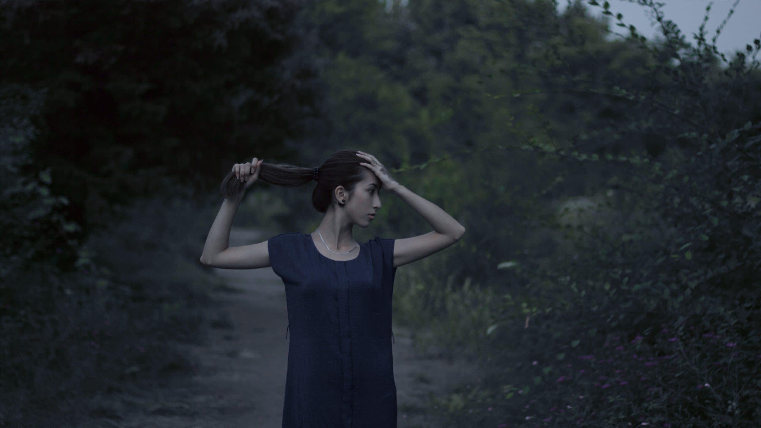 Menina com expressão assustada segurando o cabelo em um caminho cercado pelo mato.