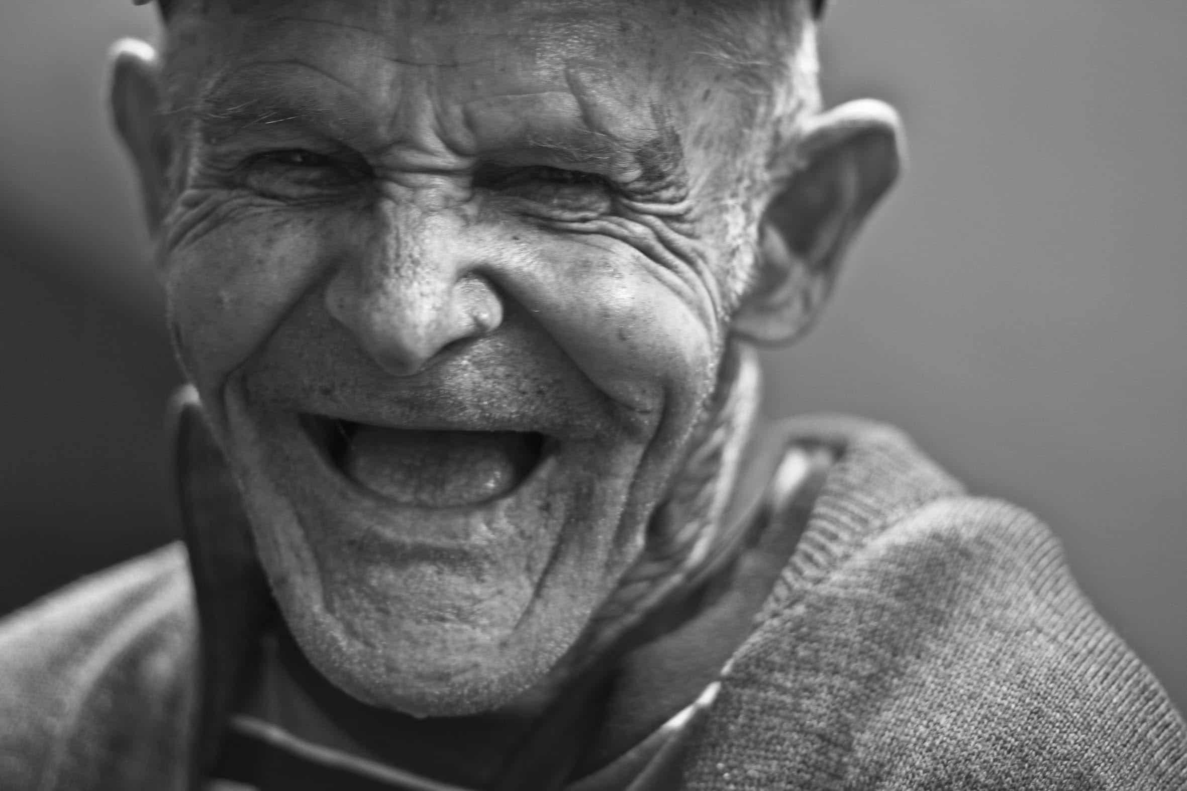 Homem idoso rindo.