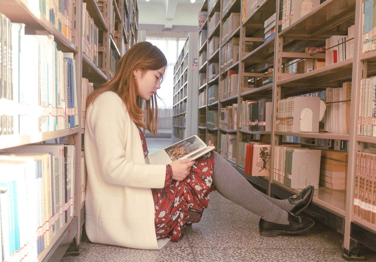 Menina sentada em chão de biblioteca lendo livro