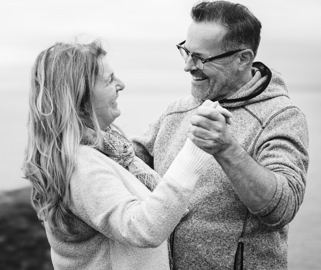 Imagem preta e branca de casal mais velho de braços dados dançando