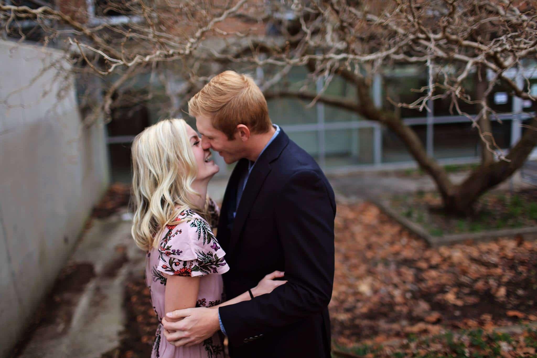 Casal feliz sorrindo com árvore e folhas de outono ao fundo
