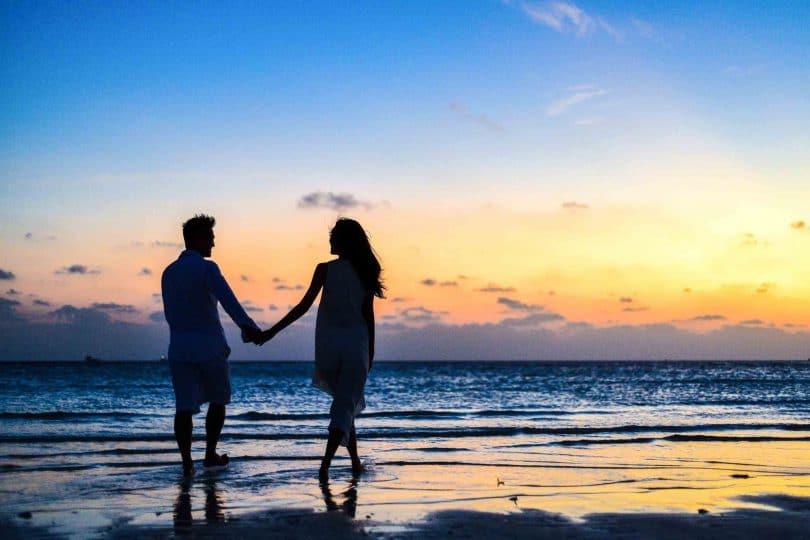 Casal andando na beira da praia com pôr do sol de fundo