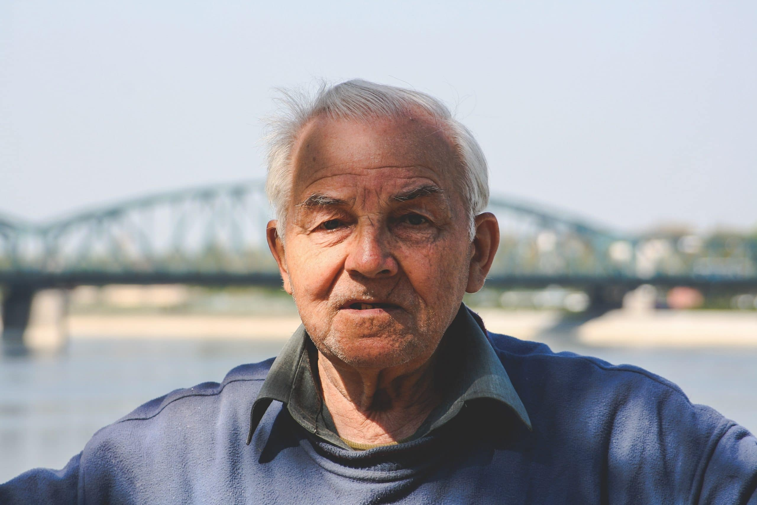 Senhor idoso em frente a uma ponte.