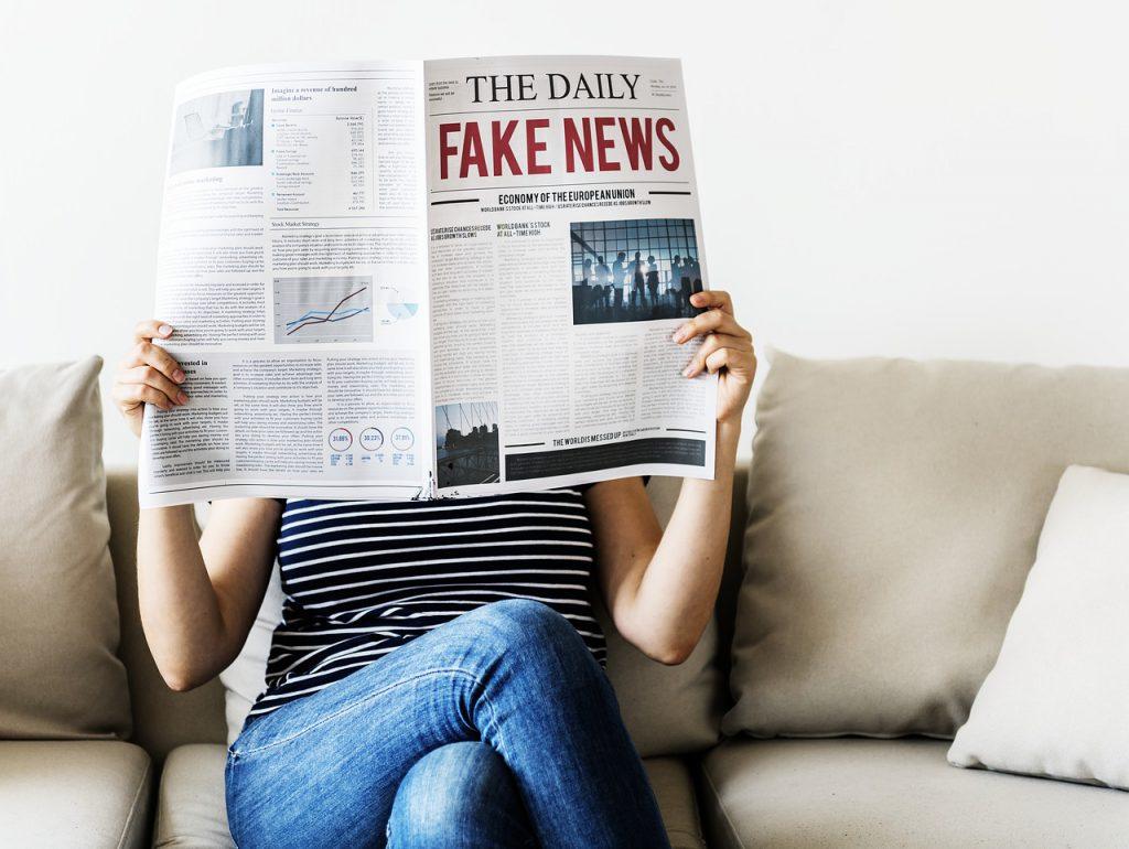 Mulher sentada em um sofá. Ela está segurando um jornal na altura do seu rosto. O jornal tem a palavra fake news destacada em vermelho na primeira página.