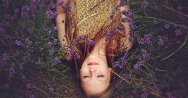 Garota deitada em grama com flores roxas sobre seu corpo de cabelo solto