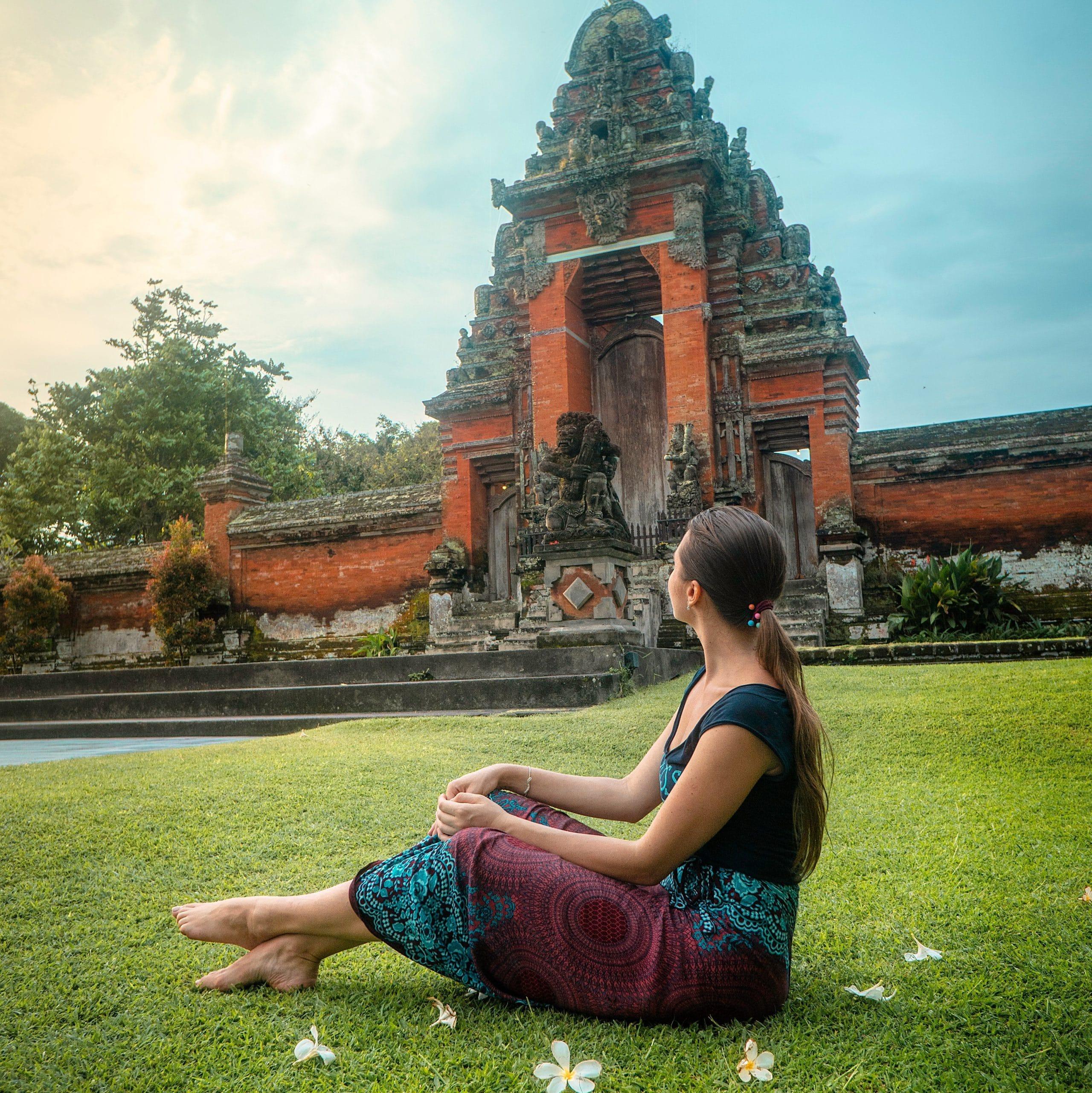 Mulher sentada em um gramado com flores ao seu redor observando um templo.