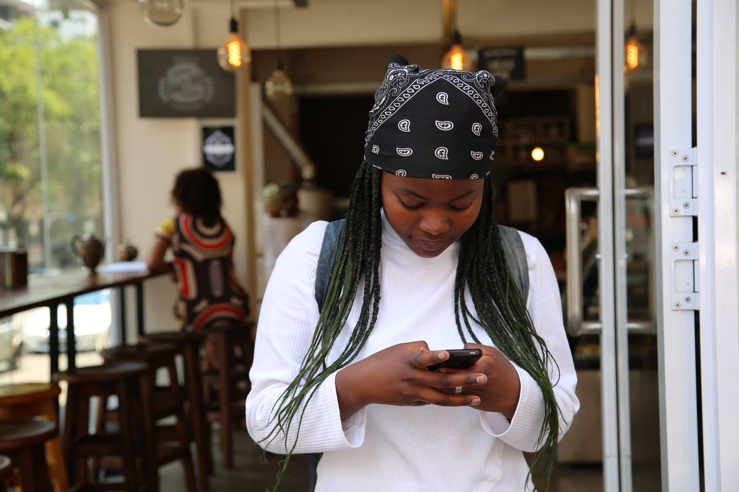 Mulher com bandana na cabeça mexendo no celular