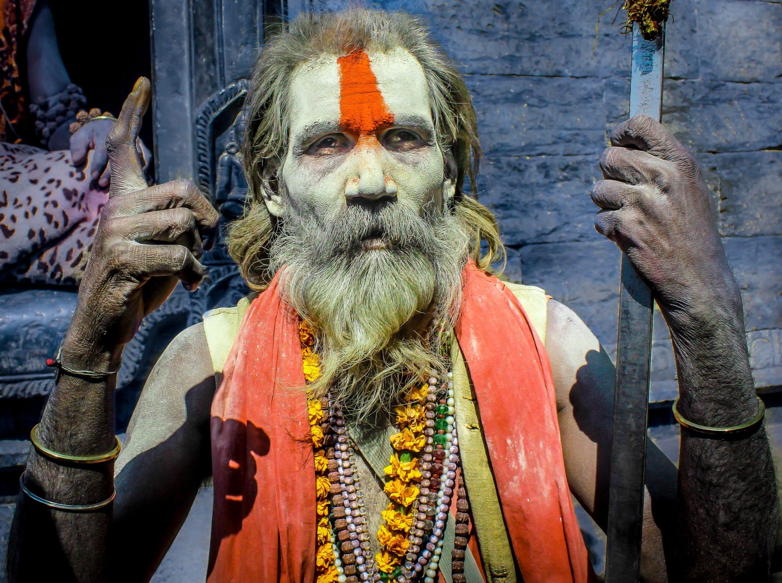 Homem hindu cheio de pinturas e roupas coloridas.