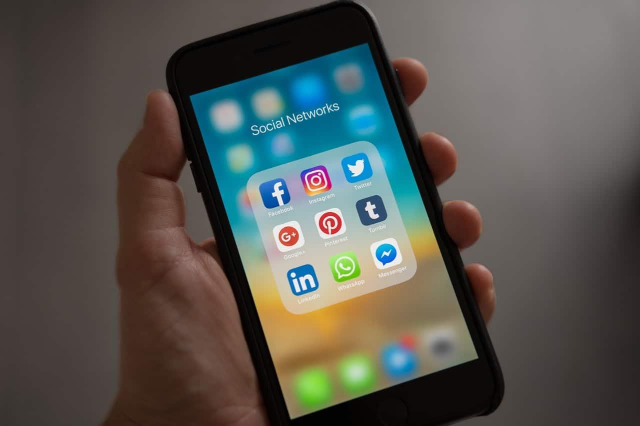 Mão segurando celular com ícones de redes sociais: Facebook, instagram, twitter, linkedin e etc