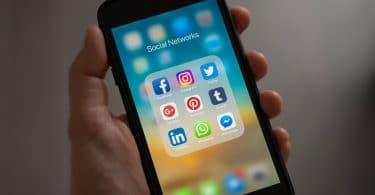 Mão segurando celular com menu de redes socias abertas