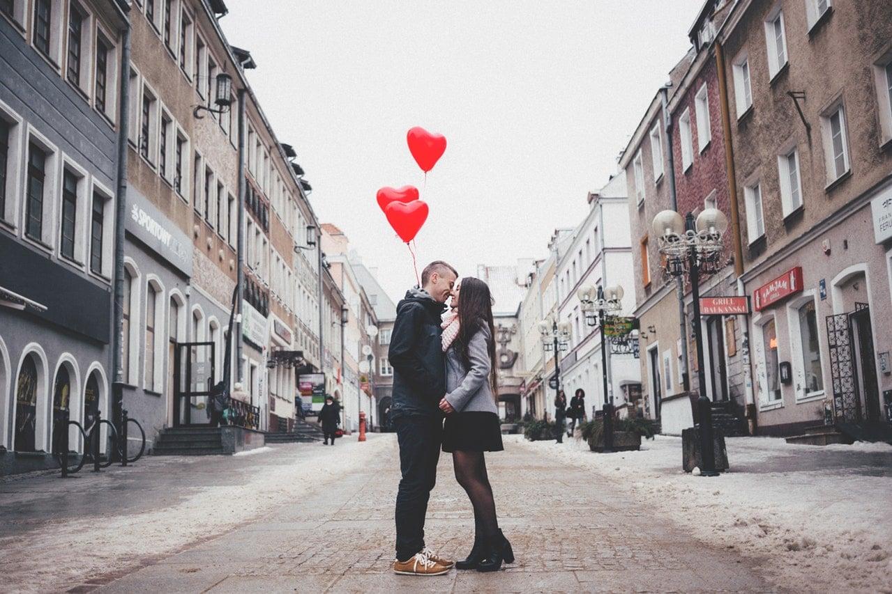 Casal no meio da rua com balões em formato de corações se olhando e sorrindo