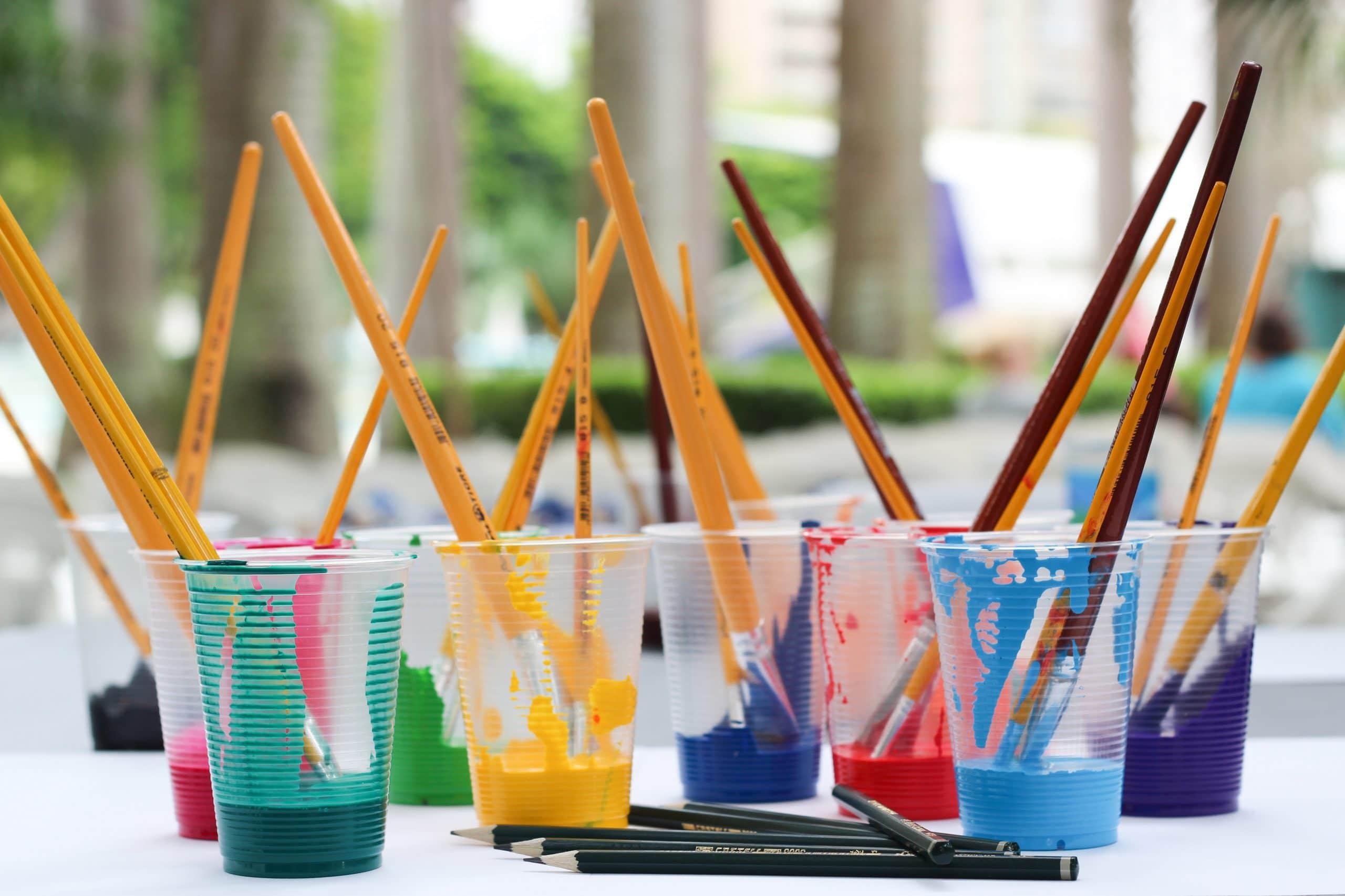 Copos de plástico com pinceis e tintas coloridas