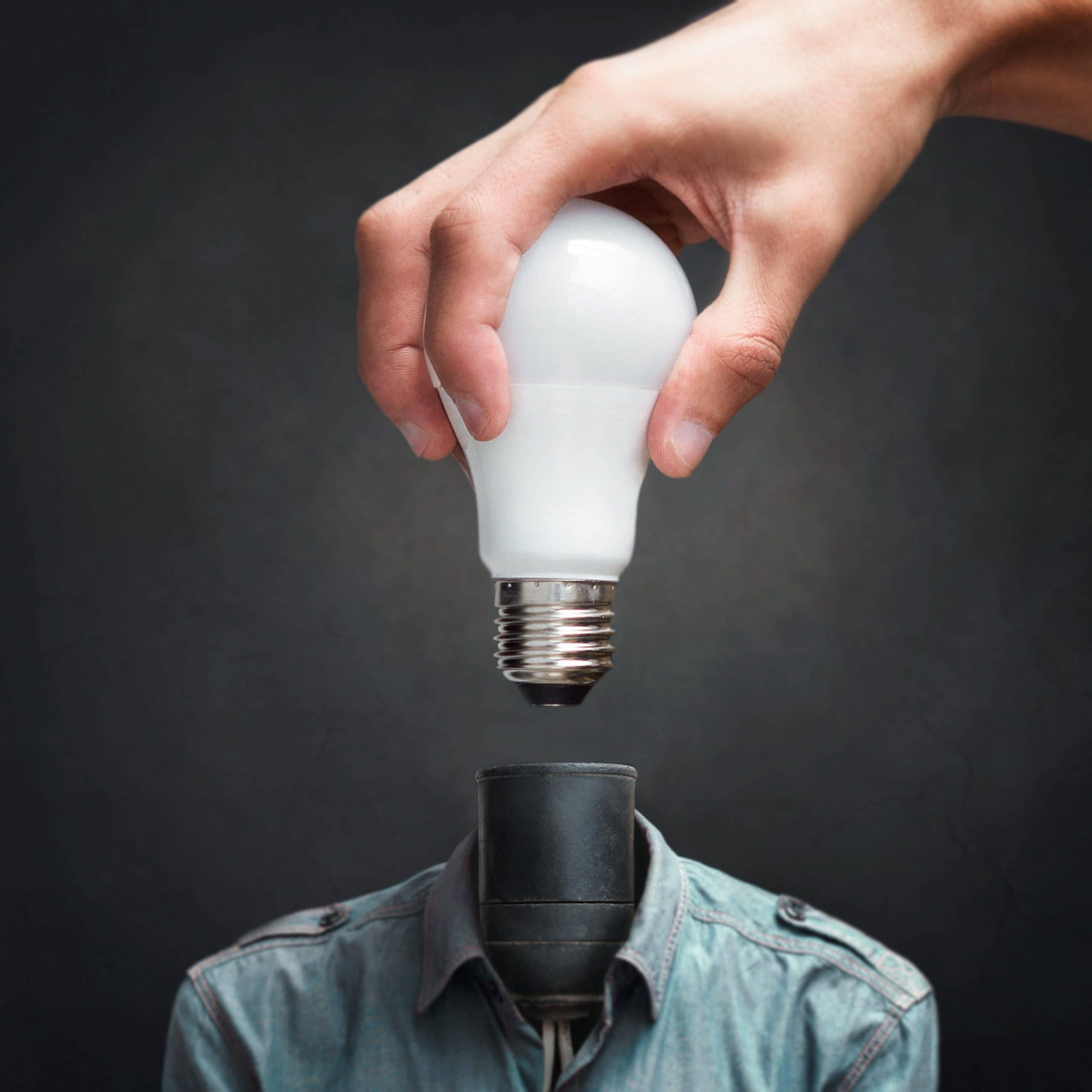 Mão encaixando uma lâmpada no lugar da cabeça.