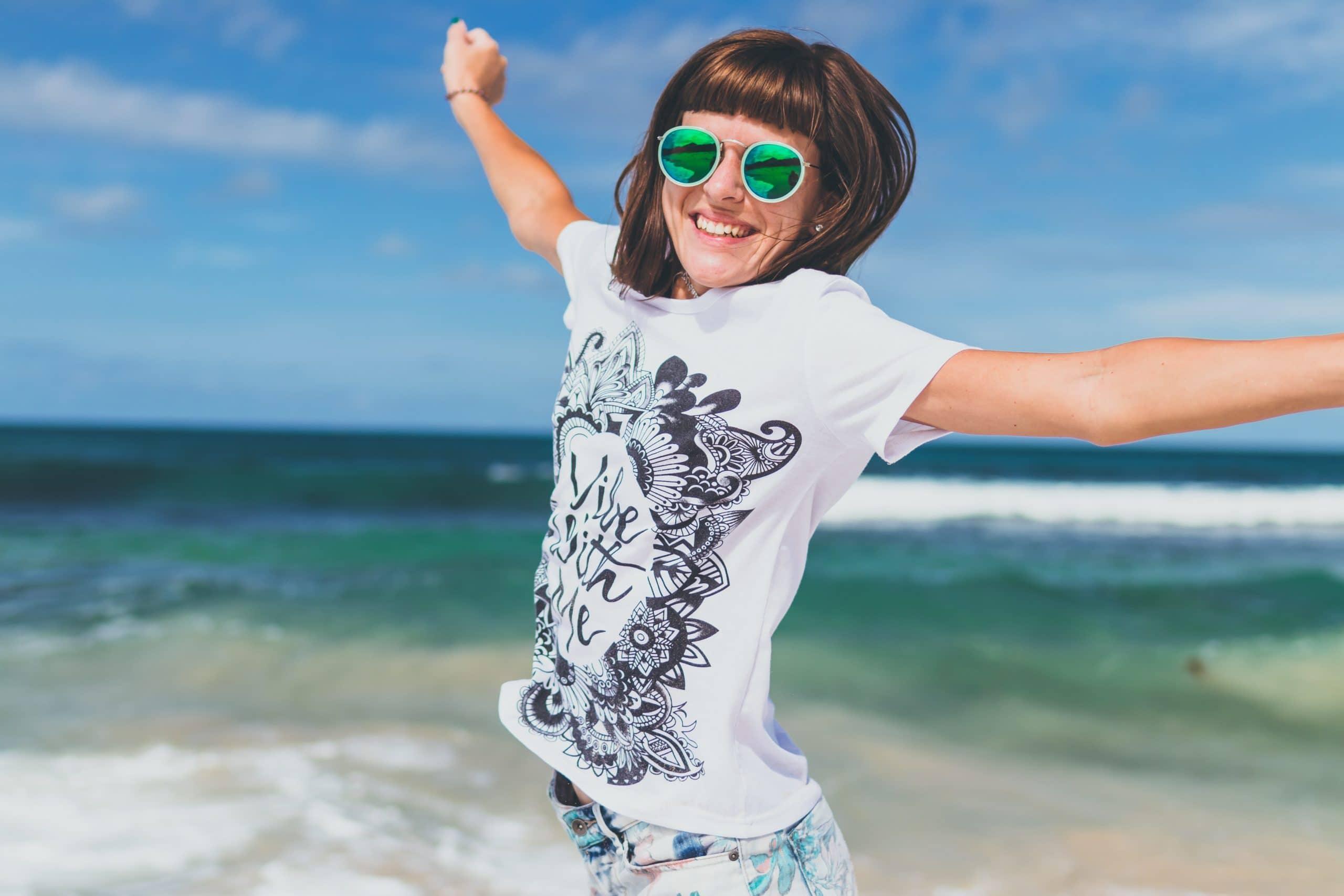 Mulher na praia sorrindo e pulando com óculos de sol