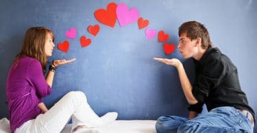 Homem e mulher se olhando e mandando beijos.