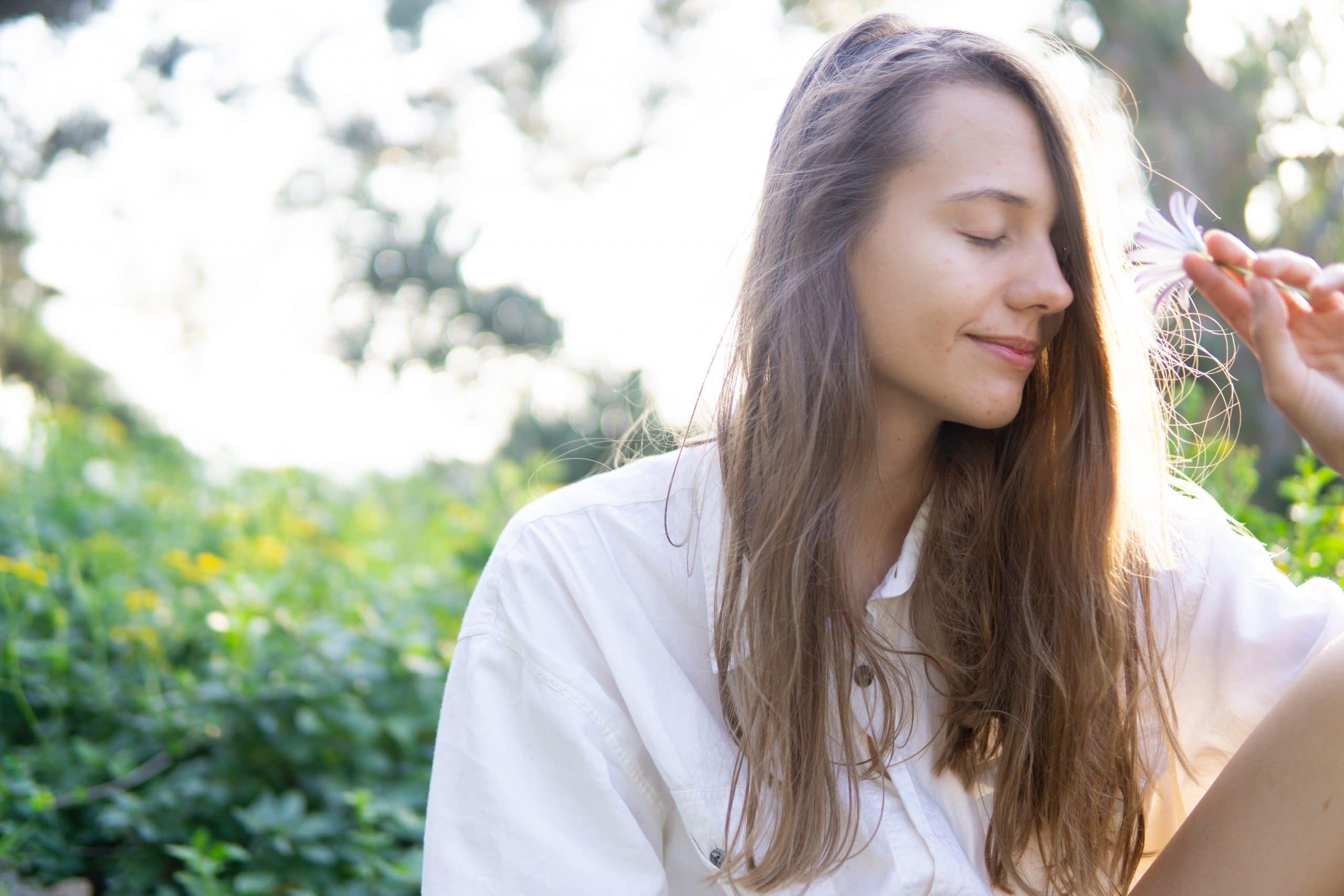 Menina vista de frente com rosto tremido olhos fechados e cabelo solto com árvores de fundo e céu claro