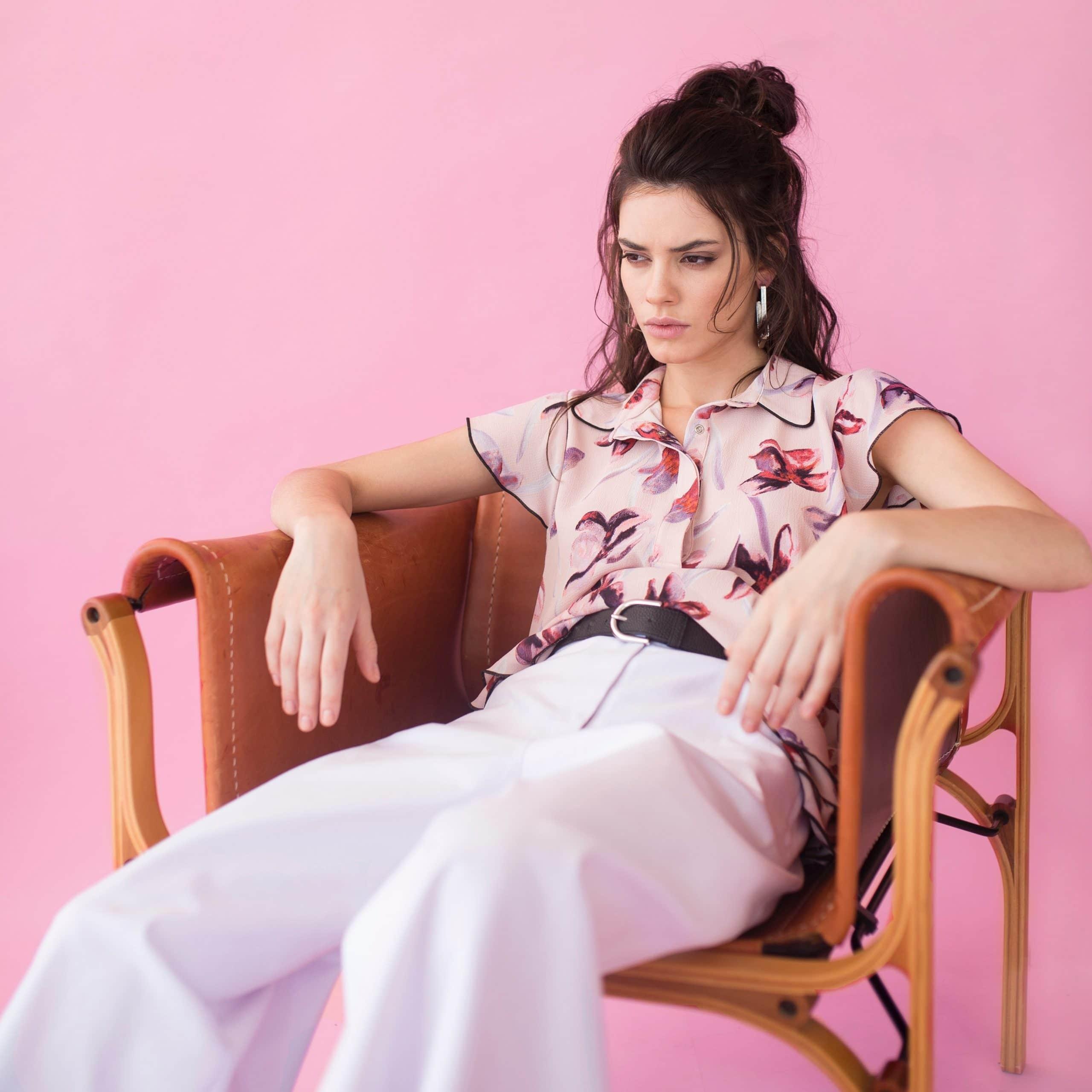 Mulher sentada em uma poltrona com as pernas abertas e expressão irritada.