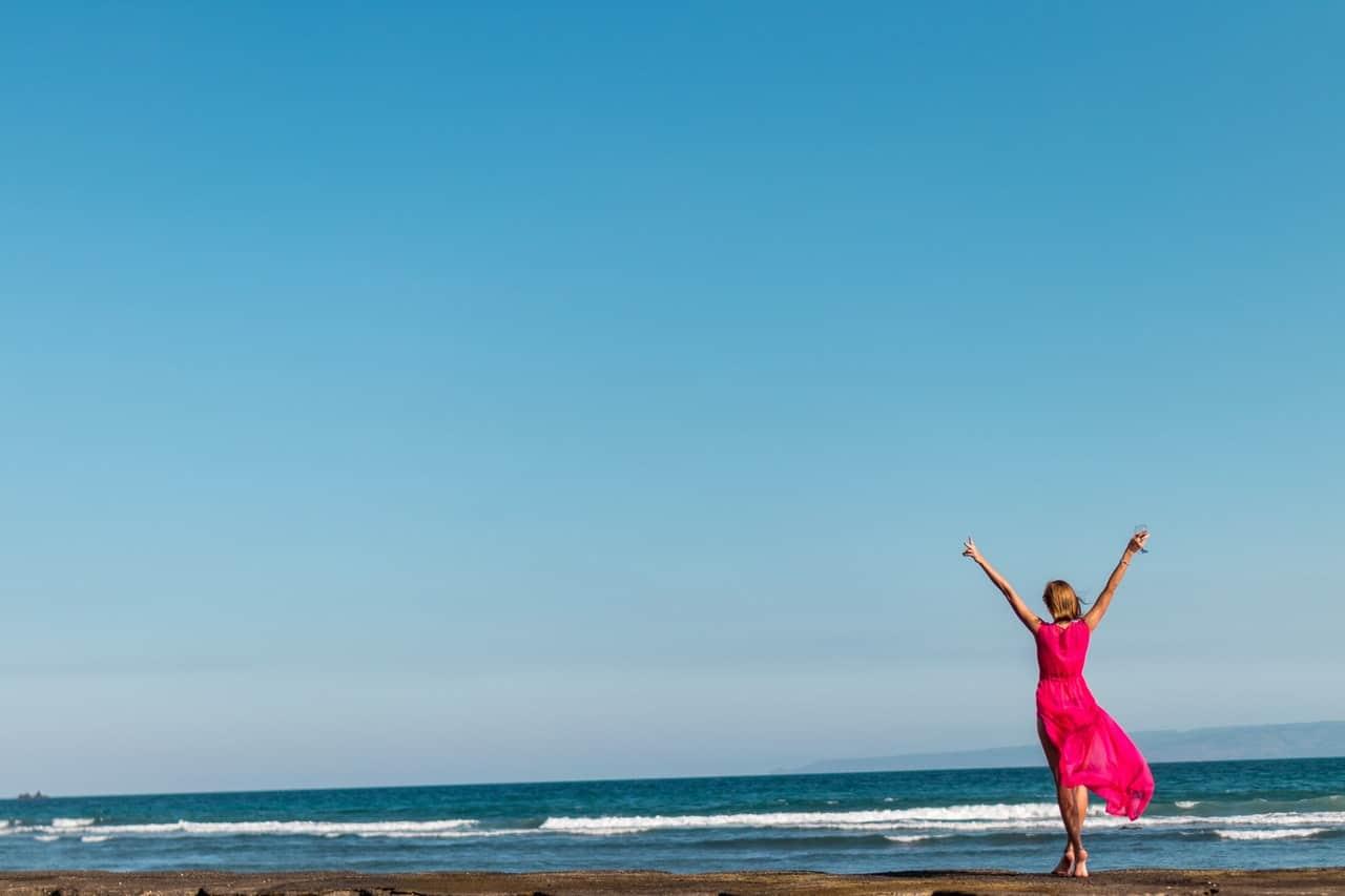 Mulher caminhando na praia de vestido longo e braços abertos de frente para o mar