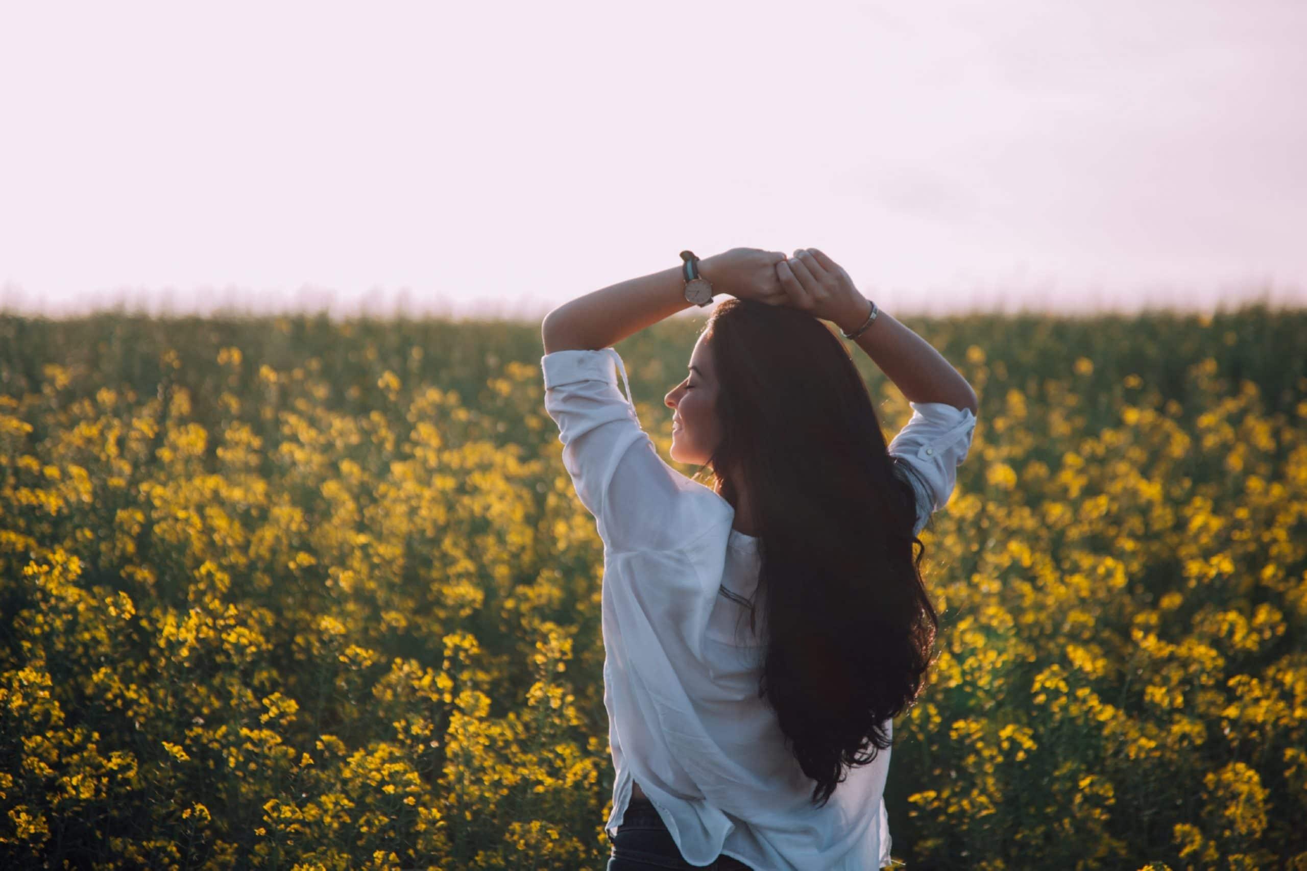 Menina de costas em frente a um gramado cheio de flores.