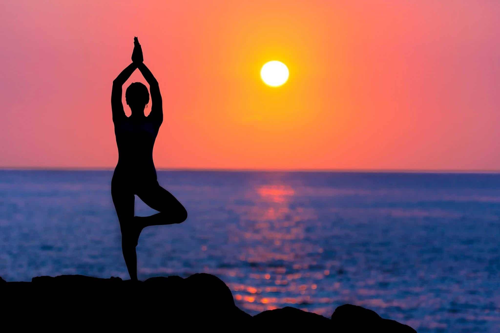 Mulher em posição de yoga com o pôr do sol no mar ao fundo.