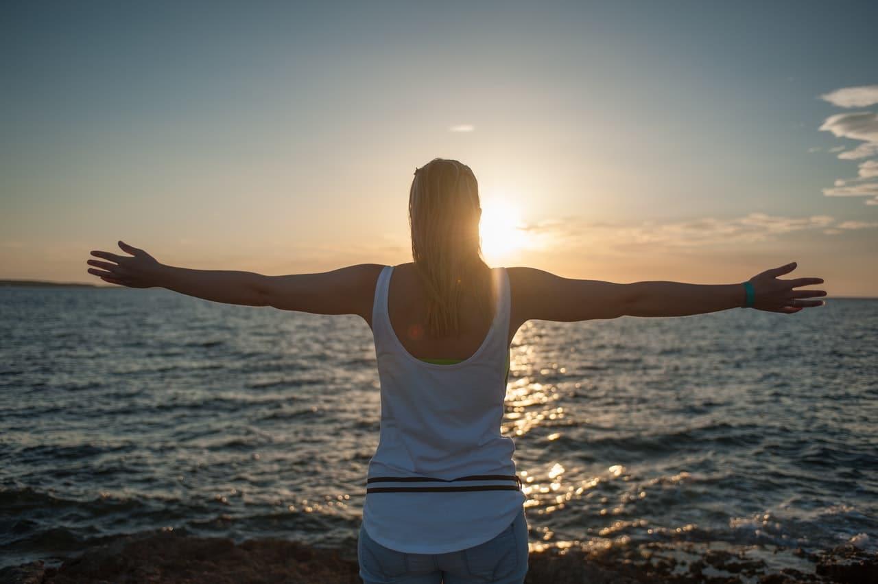 Mulher de costas de braços abertos com mar e céu com sol ao fundo