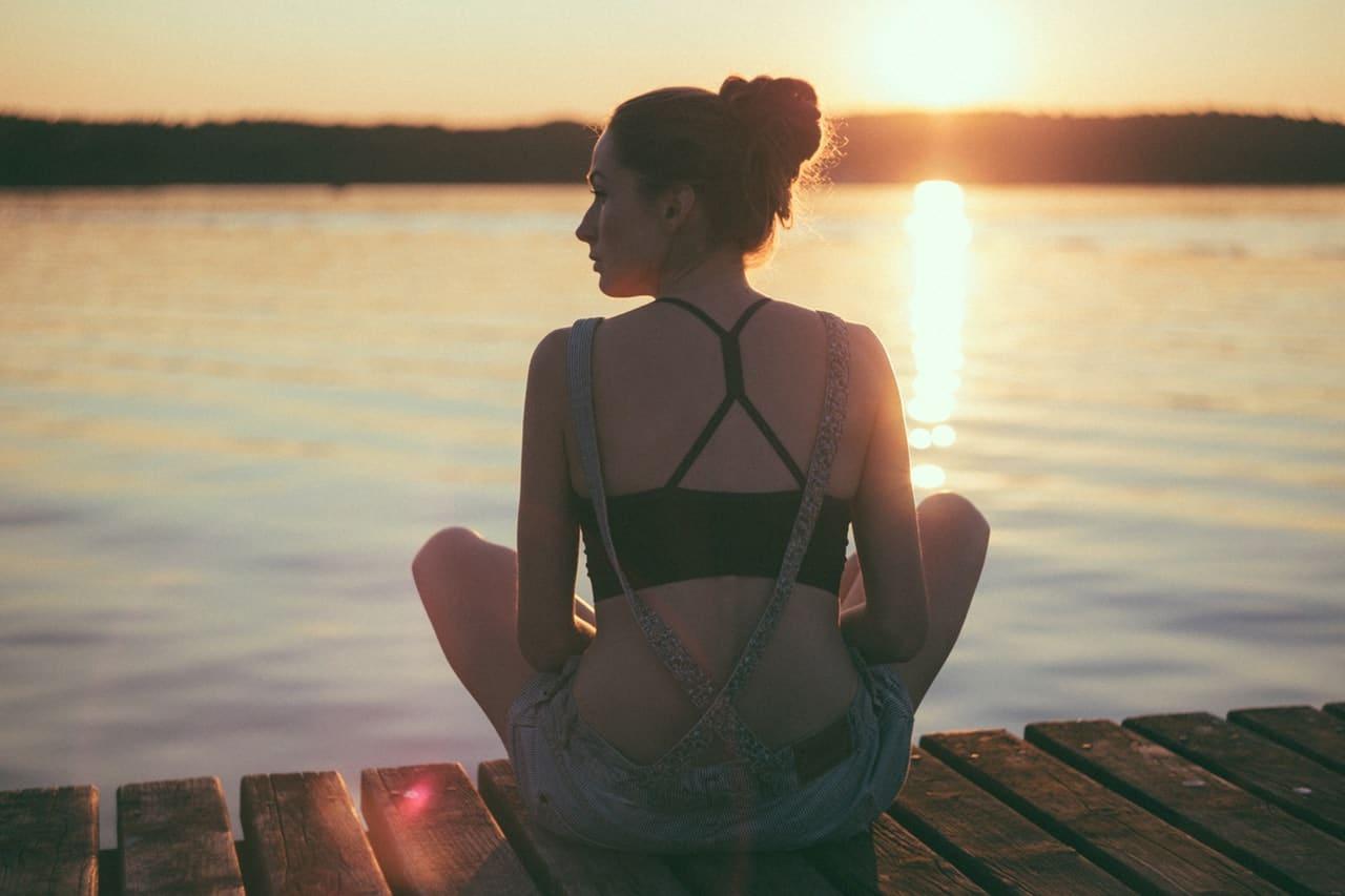 Menina de costas sentada em ponte de madeira com lago e pôr-do-sol de fundo