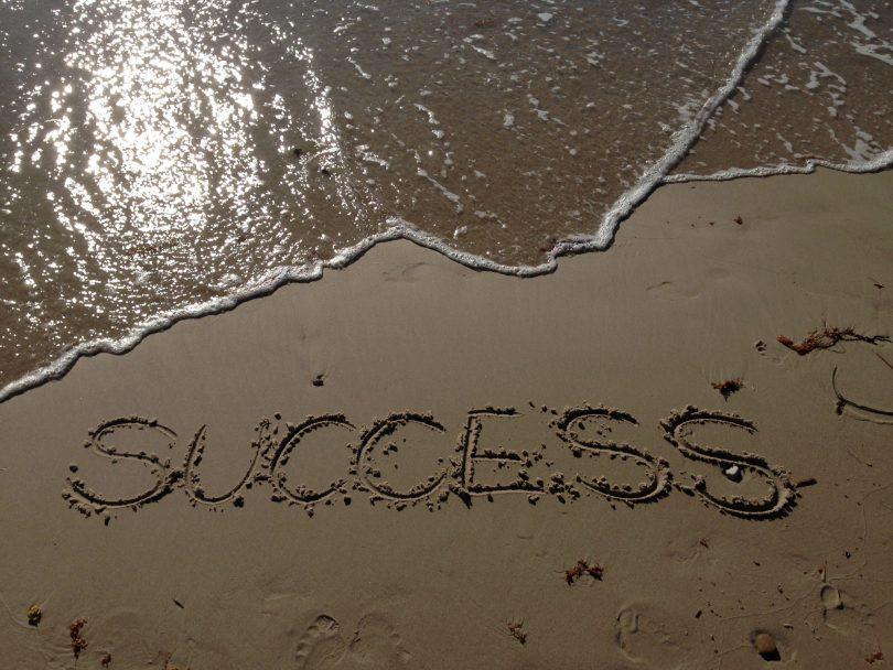 """""""Success"""" escrito na areia com água do do mar ao lado"""