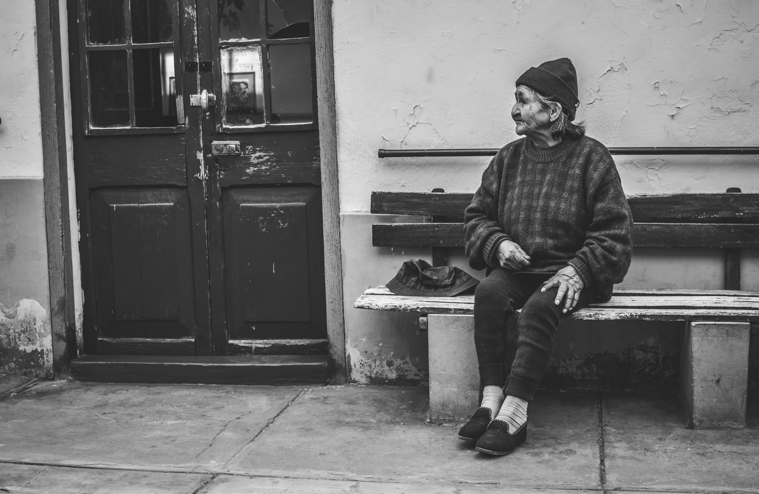 Senhora idosa sentada em um banco na rua.