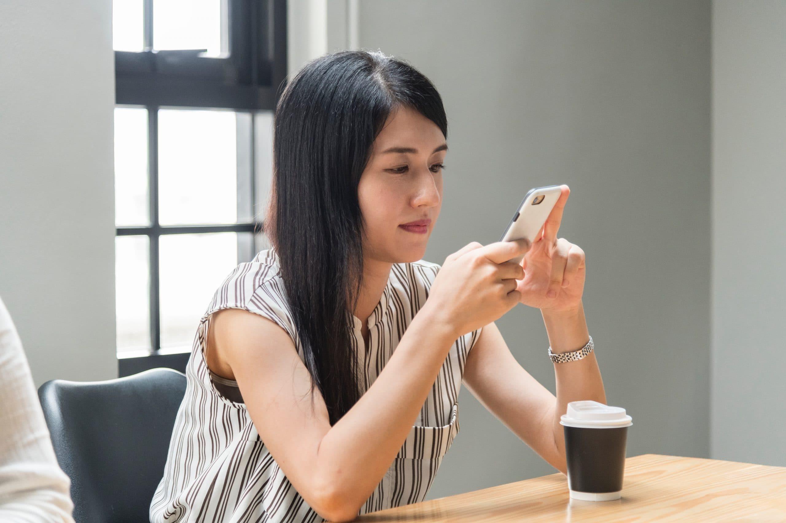 Mulher sentada com braçoes apoiados na mesa segurando celular com copo de café sobre a mesa