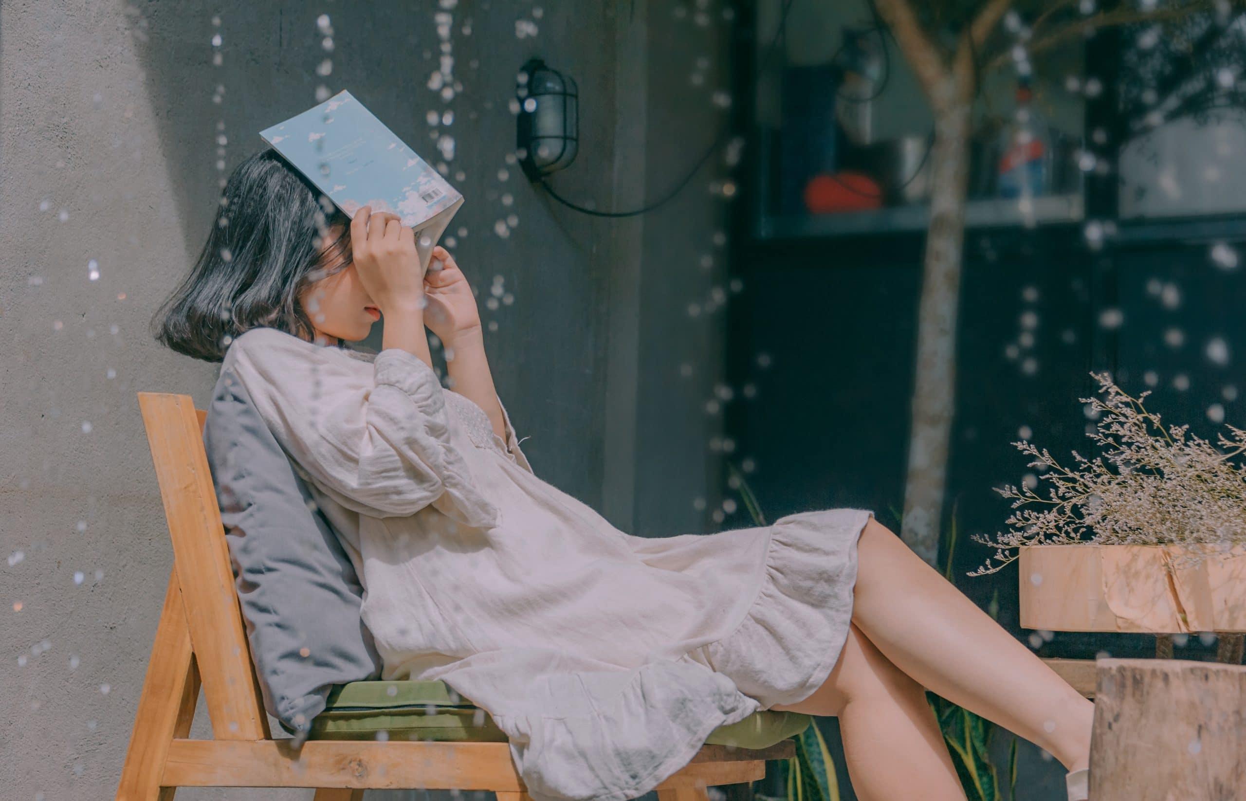 Garota sentada em uma poltrona com as pernas cruzadas e um livro cobrindo seu rosto.