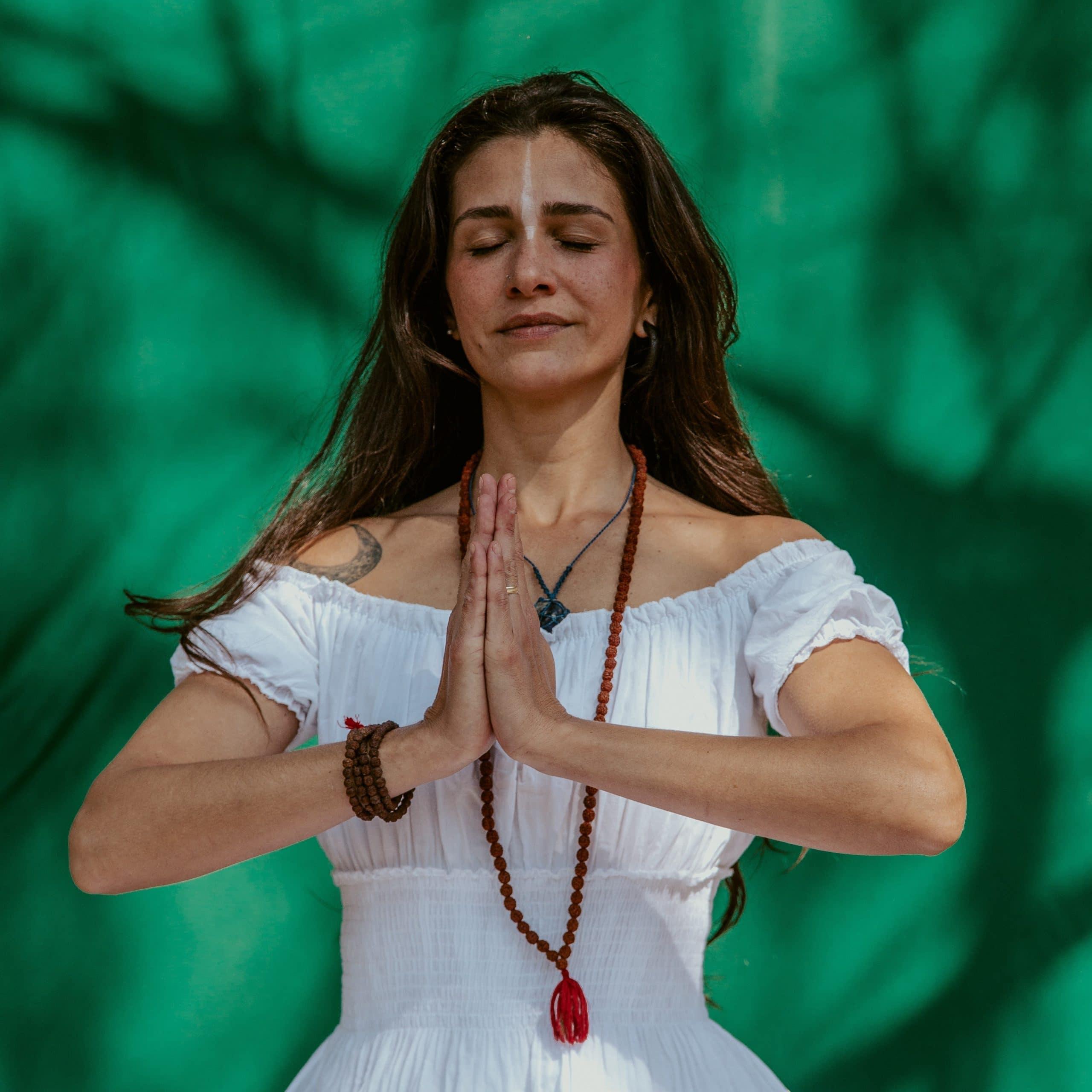 Mulher meditando com as mãos em oração.