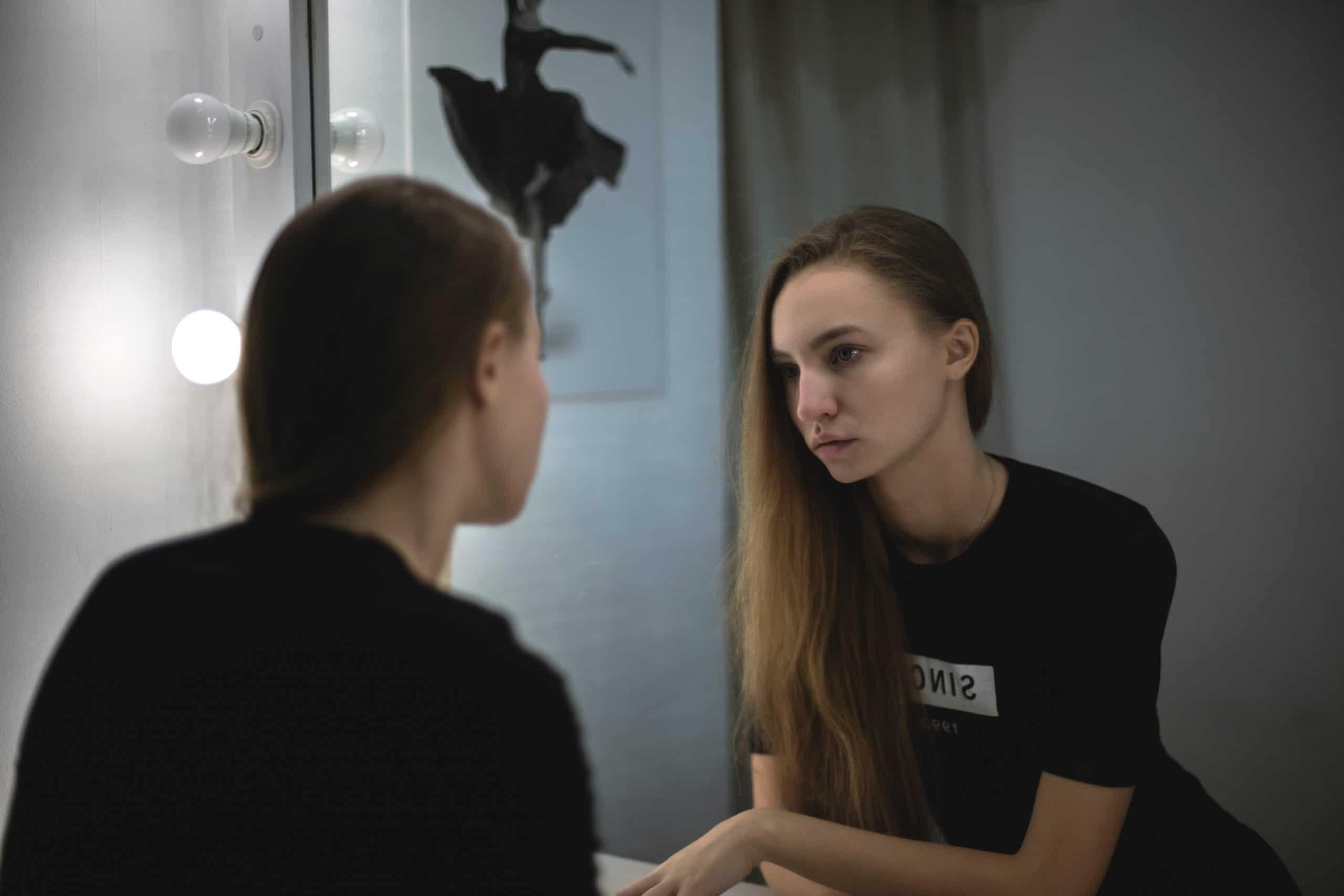 Menina se olhando no espelho do banheiro.