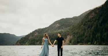 Casal em pé de mãos dadas em cima de ponte com mar e montanha de fundo