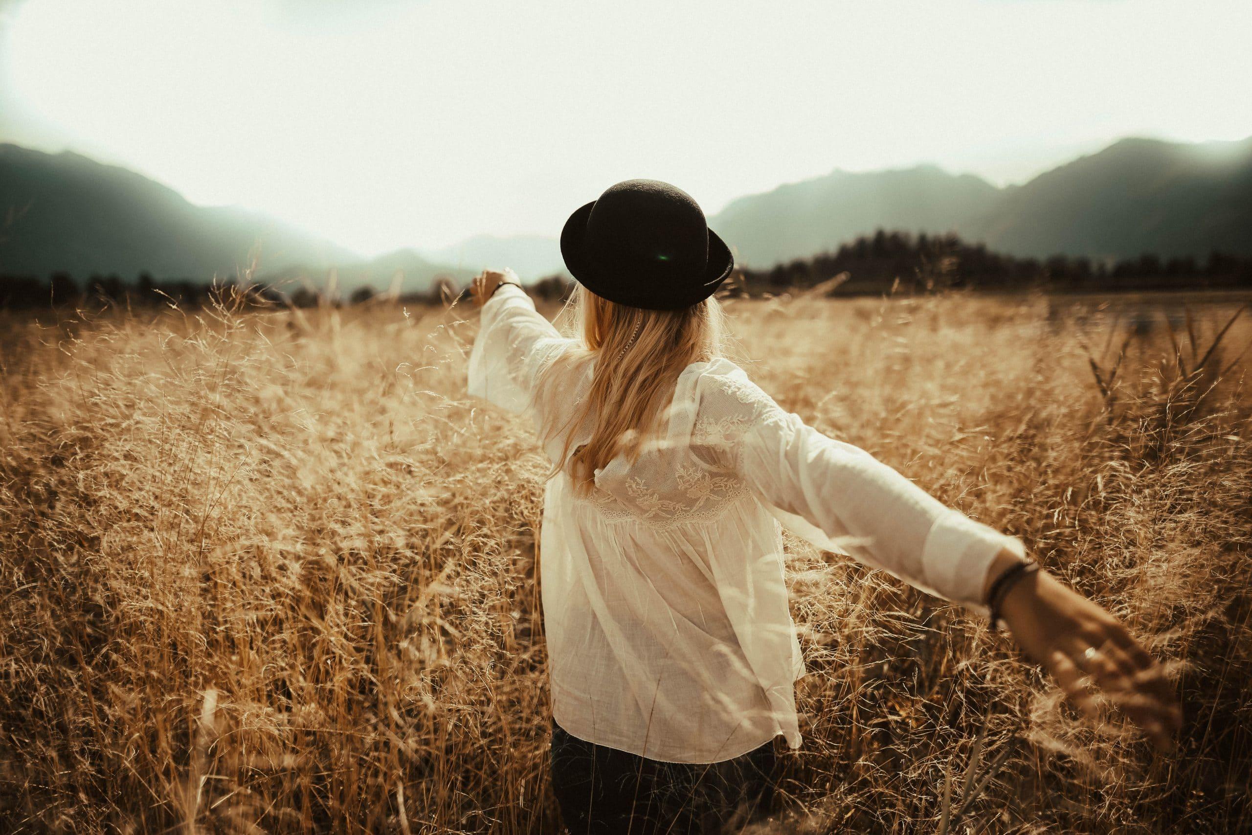 Mulher em campo com plantas secas usando chapéu e braços abertos e cabelo solto