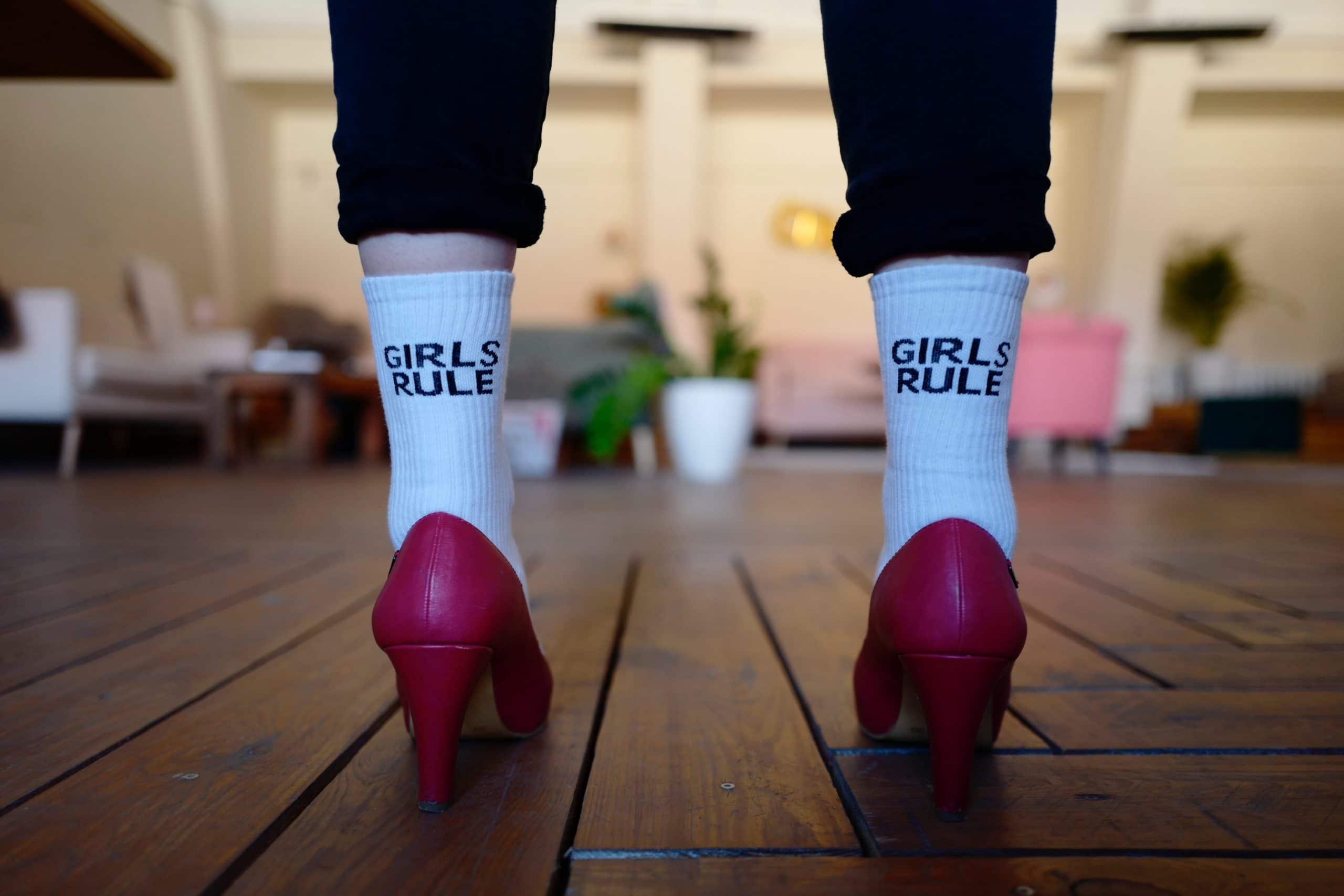 """Mulher com meia escrito """"Girls rule"""" e salto."""