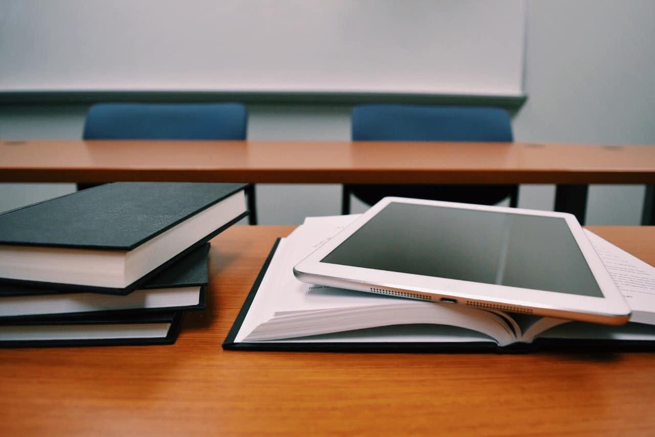 Mesa com livros e livro aberto com iPad em cima